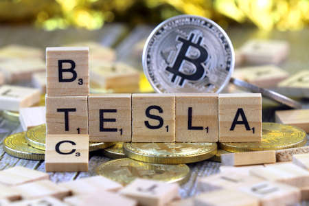 WROCLAW, POLAND - FEBRUARY 10, 2021: Word TESLA and BTC (Bitcoin) made of small wooden letters, and physical version of Bitcoin. Conceptual image for investors in cryptocurrency and electric cars.