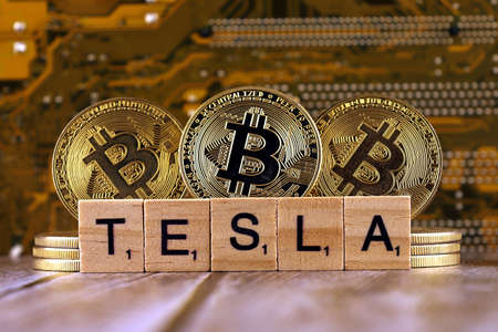 WROCLAW, POLAND - FEBRUARY 10, 2021: Word TESLA made of small wooden letters, and physical version of Bitcoin.