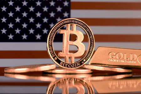 Physical version of Bitcoin, gold bar and United States Flag.