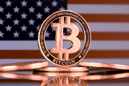 Physical version of Bitcoin and United States Flag.