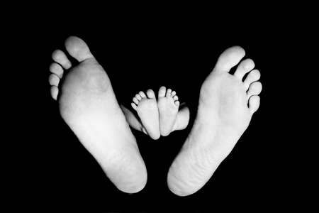 FOOTS OF A BEAUTIFUL BABY. SHOT IN STUDIO. ISOLATED ON BLACK. photo
