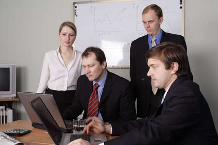 acquaintance: Group of 4 business people working together in the office.
