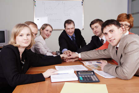 coalition: Group of business people working together in the office.