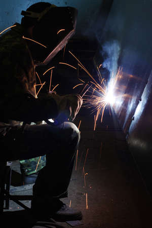 manufactory: Welder working an industrial background