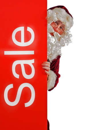 Santa peeping from behind a board with the word Sale on it photo