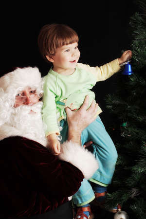 Santa carrying a boy and helping him to decorate the Christmas tree Stock Photo - 2071228