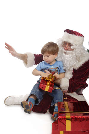 Santa with a boy sitting on his lap, holding a gift Stock Photo - 2069303