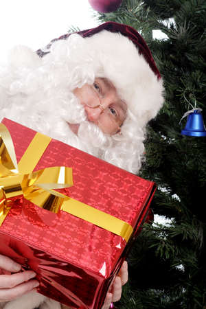 Santa holding a gift beside a Christmas tree Stock Photo - 2071232