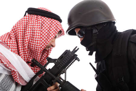 Man in traditional scarf and a soldier holding gun.  photo