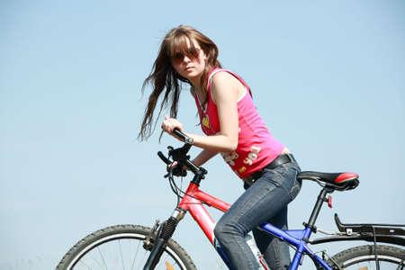 Beautiful girl cycling in the meadow Stock Photo - 3114351