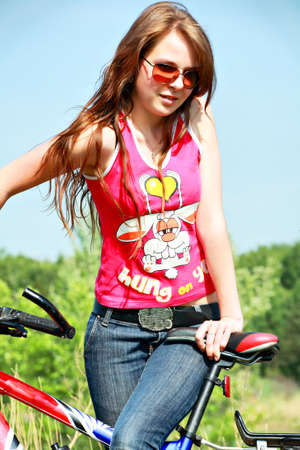 Beautiful girl cycling in the meadow Stock Photo - 3114453