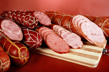 meaty: Tasty sausages on the red background.
