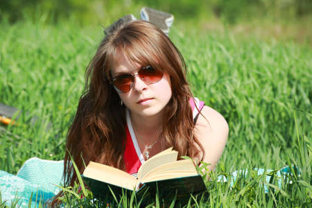 Beautiful girl read the book and lying on Grass photo