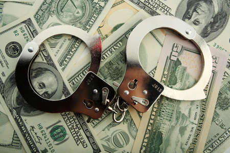 prosecutor: Silver handcuff and dollar bank notes  Stock Photo