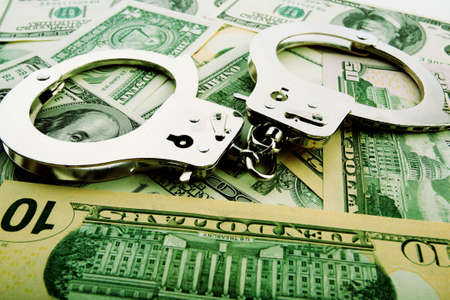 Silver handcuff and dollar bank notes  Stock Photo