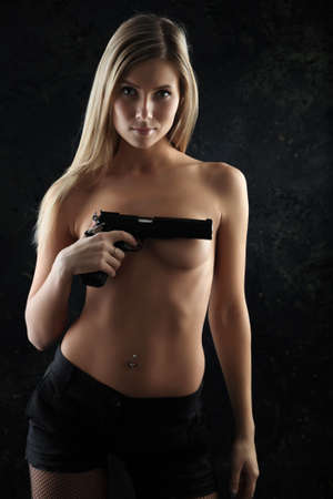 fighting styles: Shot of a beautiful girl holding gun. Stock Photo