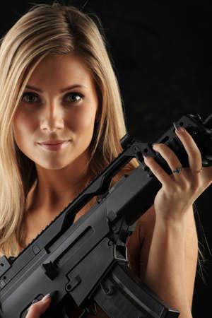 khaki: Shot of a beautiful girl holding gun. Stock Photo