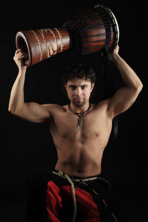 musculine: Handsome drummer playing the african drum. Shot in a studio. Stock Photo