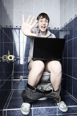 Funny young man with a laptop in WC. Stock Photo - 4829154