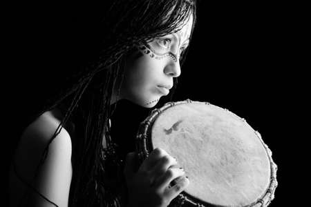 Beautiful ethnic young woman playing a drum. photo