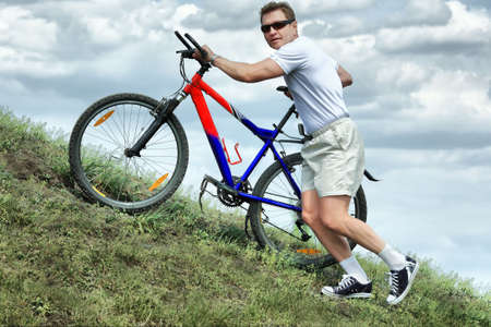 Sporty mature man cycling along cross country. Stock Photo - 4899657