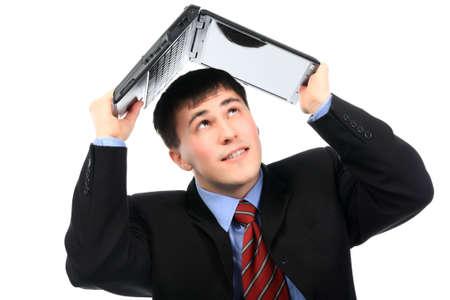 Business theme: handsome businessman is hiding under his laptop. photo