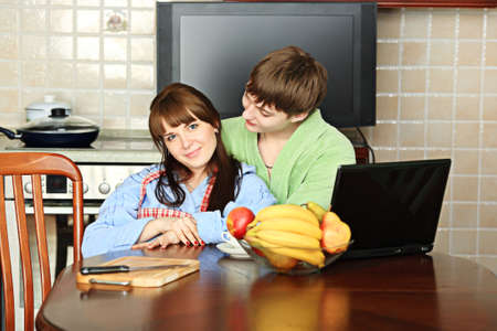 Happy young couple on a kitchen at home. Stock Photo - 5035263