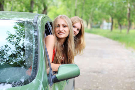 Cheerful young women having summer trip on a car. photo
