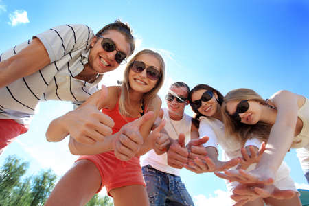 friendship circle: Cheerful young people having fun on a beach. Great summer holidays.  Stock Photo