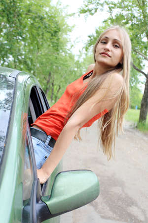 Cheerful young woman having summer trip on a car. photo