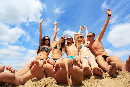 young girl feet: Cheerful young people having fun on a beach. Great summer holidays.  Stock Photo