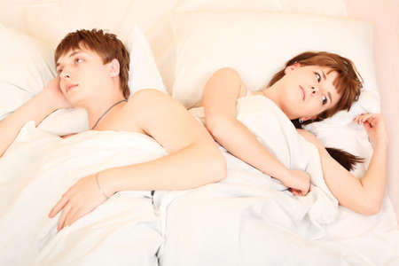 Young couple in a bedroom at home. Family conflict. photo