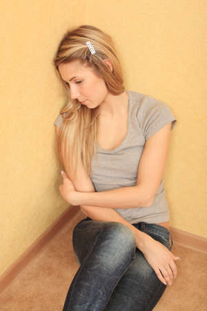 Portrait of sad young woman sitting on a floor at home. photo