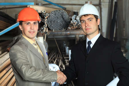 Industrial theme: two businessman shaking their hands at a manufacturing area.   photo