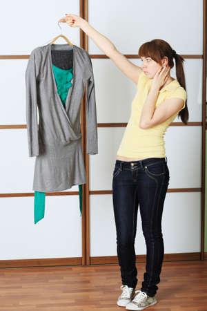 vouge: Beautiful young woman choosing a dress.
