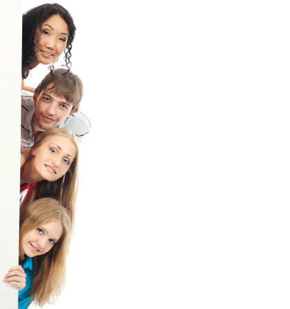 Group of a cheerful young people holding a billboard with empty space for your ad.  photo