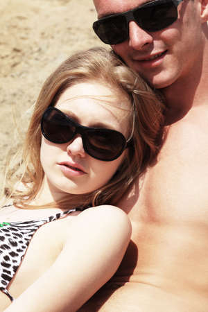 Couple of young people having a rest on a beach. Great summer holidays. photo