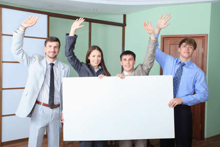 acquaintance: Business theme: business people holding empty billboard. Shot in an office.