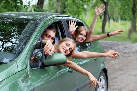 hire: Cheerful young people having summer trip on a car.