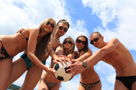 Cheerful young people playing volleyball on a beach. Great summer holidays. Stock Photo - 5371191