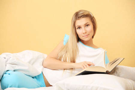 Young woman having a rest with a book at home. photo