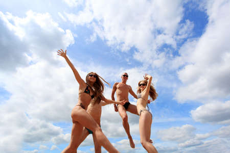 Cheerful young people having fun on a beach. Great summer holidays.  photo