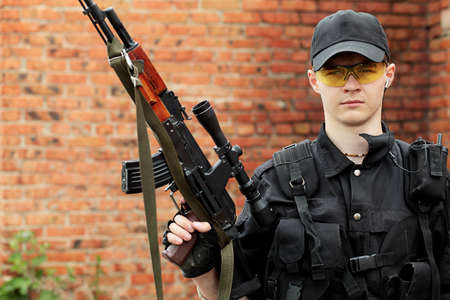 conforms: Shot of a soldier holding gun. Uniform conforms to special services.