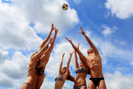 beach ball girl: Alegre j�venes jugando voleibol en la playa. Vacaciones de verano. Foto de archivo