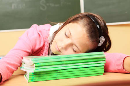 Educational theme: schoolgirl sleeping on her textbooks in a classroom. photo