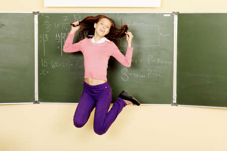 Educational theme: cheerful schoolboy jumping in a classroom. photo