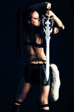 Beautiful female fighter with a sword in her hands. photo