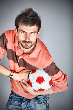 Portrait of a handsome sportsman holding a ball. photo