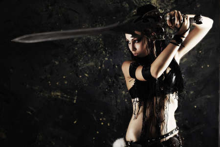 ancient warrior: Beautiful female fighter with a sword in her hands. Stock Photo