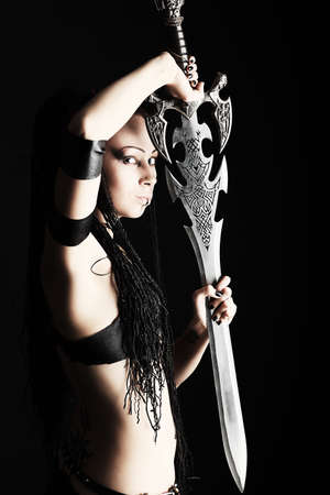 medieval sword: Beautiful female fighter with a sword in her hands. Stock Photo